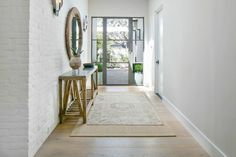 Lovely foyer features white brick walls framing round wood mirror illuminated by sconces over wood and concrete console table alongside layered rugs. Front Entrance Ways, Entrance Foyer, Entry Ways, Front Doors, Front Porch, Entry Stairs, Entry Hallway, Foyer Mirror, Wood Mirror