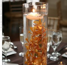 Short vases held oranges while taller ones were filled with orchids; both had candles floating at the top