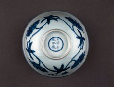 Porcelain bowl. Underglaze blue with band of scrolling hibiscus flowers with star-shaped leaves around outside and similar band around inside cavetto. Roundel in centre with large flower head in double circle. Inscription on base.