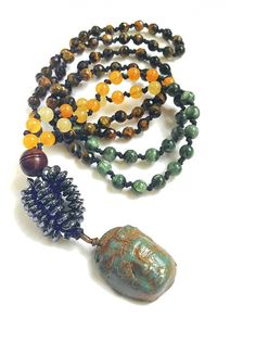 A beautiful and unique hand knotted mala created from faceted tiger eye, smooth seraphinite, yellow jade and a mandmade hematite. The guru bead is a ceramic Buddha, handmade and glazed with a rustic feel. The gemstones on this mala create a strong intention of courage, trust and vitality.