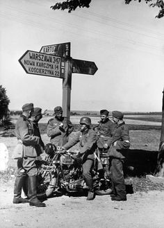 German soldiers pause for a seemingly leisurely rest during the invasion of Poland. They stand beneath a road sign in the north of Poland in the Polish Corridor, which divided the bulk of Germany from the German province of East Prussia and provided Poland with access to the Baltic Sea. Near Nowa Karczma, Kościerzyna County, Pomerelia (now, Pomeranian Voivodeship), Poland. September 1939.