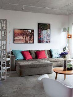 O apartamento tem poucos móveis para manter o espaço livre. No estar, o sofá de tom neutro foi comprado na Marché Art de Vie – as almofadas (Poeira) e as fotos de Diego Kuffer (Galeria Lume) se encarregam de trazer o colorido. Luminária Caruaru (Micasa) e tapete da Rug Revolución.