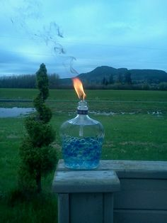 """My home made tiki torches. I used Crown Royal bottles, Tiki replacement wiks, and a 3/8 washer to hold wik in place. I filled the bottles with marbles and """"OFF - Bug fighter"""" tiki torch fluid. Cant wait for summer Bbq's. :D"""
