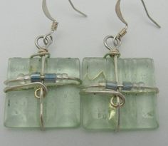 These are donated recycled clear 1/2  square glass tiles, silver wire wrapped, each adorned with 2 denim blue beads and 4 clear seed beads.  Also
