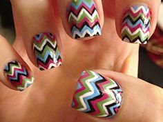 """1. Apply a base coat.  2. Once dry, apply two coats of a deep brown polish.  3. Next, use a Sharpie Peel-Off China Marker (you can find these online or at an art supply store), in white and black, to draw a repeating chevron (aka zigzag) pattern going across the nail.  4. Use the nail art brushes to create a thin line that follows the chevron pattern, making sure to switch colors as you complete the line. Work down the nail. This will create that """"Missoni"""" look.   5. Finish with a top coat."""
