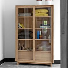 Oak Wave Book Rack by Ethnicraft NV is clean, simple and built for life. This bookcase has two sliding glass doors and two drawers built in.