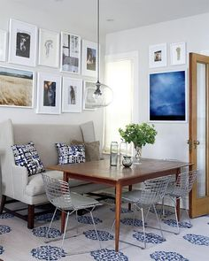 Modern/eclectic breakfast nook.  Print rug, modern-wingback banquette, globe lights, metal chairs, etc.