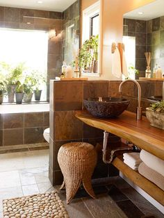 36. The natural curvy wooden slab vanity is to-die-for, and the matching wooden shelf underneath is perfect for storing extra towels. The stone tiled walls, and lush greenery in the window set the tone for ultimate relaxation.