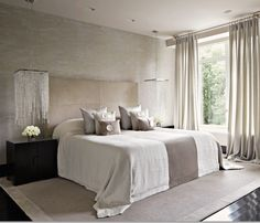 Light bedroom with dark wood floors and chandeliers over the night tables.