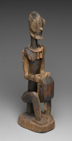 Africa | Figure of a Seated Musician (Koro Player) from the Dogon people of central northern Bandiagara escarpment, Mopti region, Mali | Wood and iron | 18th century | This figure wears a necklace called a korte. Consisting of a series of packets containing verses from the Qur'an, the korte is worn for protection—indicating the influence of Islam even among the Dogon, a largely non-Islamic people.