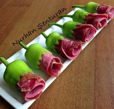 .This has no description,  but it looks like a pepper cut as the base, and rolled lunch meat.  I might use the small colored peppers as the base.  and roll cheese and meat as the flower.