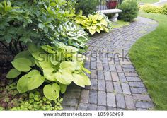 Garden Cement Paver Brick Path with Grass Lawn and Hosta Plants by JPL Designs, via ShutterStock