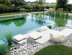 moderner Schwimmteich mit Stellen zum Sitzen und Liegen