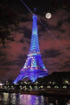 Eiffel Tower lit in blue with full moon.