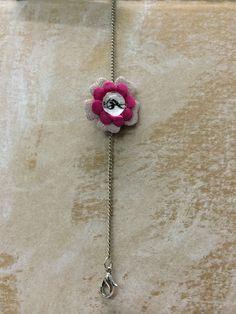 Pulsera de niña, con cadena plateada, y flor de piel con nota musical.