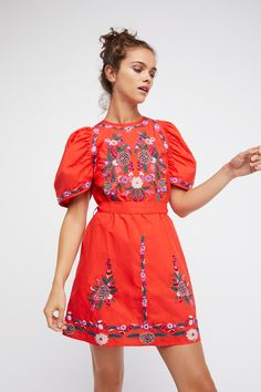 The Evangeline Dress | **Fit:** Fitted waist with an oversized sleeve.   Beautiful embroidered mini dress featuring a comfortable cotton fabrication with a colorful floral design.    * Pretty puffed sleeve shape   * Back keyhole cutout   * Tie belt at the waist