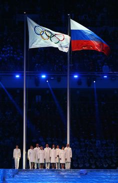 Olympic flag raisers and bearers stand next to raised the Olympic flag during the Opening Ceremony of the Sochi 2014 Winter Olympics at Fish...