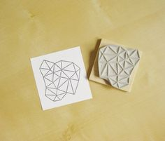 A geometric crystalline stamp intricately hand-carved out of rubber.