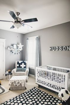 A navy, black, and gray nursery with graphic blankets and rug