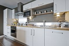 One-wall kitchen with white kitchen cabinets and brushed aluminium appliances for the small home. Photo courtesy of Affordable Building and Maintenance