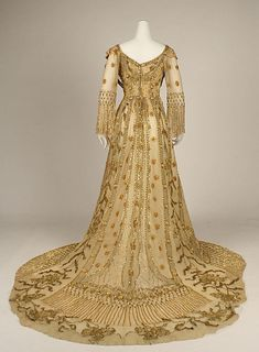 Evening dress (1907) liberally embroidered with various shades of gold thread. Flowers, leaves, web patterns etc.
