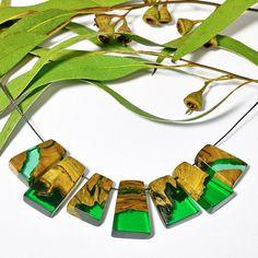 This unique necklace features Australian red gum eucalyptus and emerald coloured…
