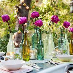 A mesa pode ganhar um novo visual com as garrafas de vinho vazias se transformando em lindos vasos de flor.