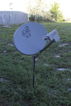 A lone satellite and dirty, in a field without any kind of connection.