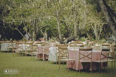 As mesas dos convidados no meio das árvores e do varal de luzes