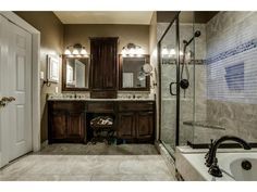 Master bathroom in brown and gray // Dual sinks // Glass shower // Decorative tile