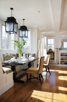 Eclectic: farmhouse (trestle) table, gray-white graphic print, lantern light fixtures, & upholstered nailhead dining chairs