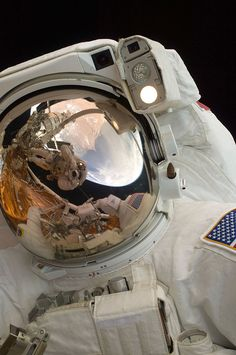 SPACE TOPIC.  Original Pin: A close-up of Astronaut John Grunsfeld shows the reflection of Astronaut Andrew Feustel, perched on the robotic arm and taking the photo. The pair teamed together on three of the five spacewalks during Servicing Mission 4 in May 2009.