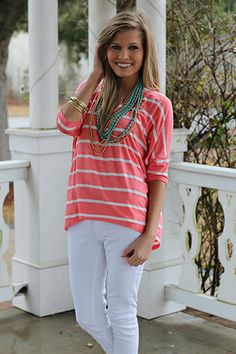 "This top feels like your PJs, but with way more style! The coral and white stripes give this top such a nautical feel, and we love the dolman sleeves and super soft material. Just add white skinny jeans and a long necklace for a beautifully casual look!   Fits true to size. Miranda is wearing a small.   From the shoulder to the hem:  Small-21""  Medium-22""  Large-23"""