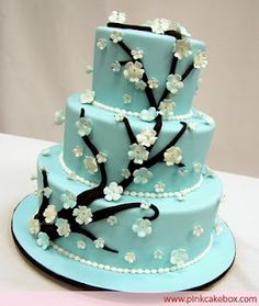 Black branches on a blue cake and looks like from a cherry blossom tree which is also Asian inspired