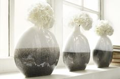 The bulbous shape and fluid lines of this vase are stunning to the eye and it's finished to perfection with the use of contrasting colours. The clean milky white gloss of the top half sits beautifully with the neutral grey gloss of the lower half. Display in a simple line of three for a scene of instant harmony.