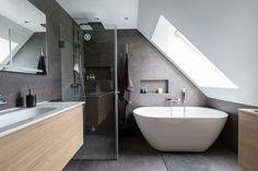 Grå skifferplattor på både väggar och golv. Under ett stort fönster i snedtaket står ett runt, fristående badkar med handdusch och förvaringsnisch. I badrummet finns även en dusch med takdusch och två glasdörrar, även den med en nisch för badrumsartiklar. Ett större vägghängt handfat med ett underrede i ljust trä kombineras med ett vägghängt badrumsskåp i samma serie. Alla rör i badrummet är infällda. Loft Bathroom, Bathroom Plans, Laundry In Bathroom, Master Bathroom, Clever Kitchen Ideas, Loft Interiors, Loft Room, Home Board, Attic Rooms