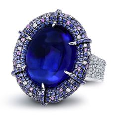 Blue oval sapphire set with diamonds and small sapphires ring.