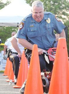 Souderton Independent photo — SUSAN KEEN Telford police Chief Randall Floyd races in the public safety bike race during Franconia's National Night Out Tuesday, Aug. 6.