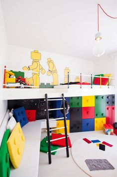 Awesome lego-inspired room with colorful oversized legos, play area, and bunk bed. It looks like below the bed is the dresser. I totally love this for a kids room!