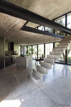 The main living area features a full glass frontage facing the mountains and stairs lead Tagged: Staircase and Concrete Tread. Photo 3 of 10 in A Commanding Mexican Home of Stone and Concrete Is For Sale