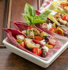 Mediterranean Endive Boats | Two bite salads filled with tomatoes, artichoke hearts, olives and feta | from That Skinny Chick Can Bake
