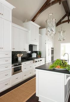 Two Mansfield lanterns hang from a gorgeous dark stained truss ceiling positioned over a white kitchen island accented with a sink and gooseneck faucet mounted in a black quartz countertop.