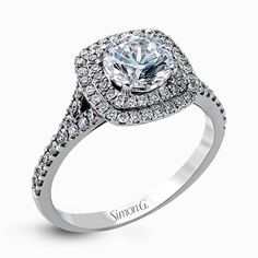 This eye-catching contemporary white gold engagement ring and wedding band set features an impressive halo accented by .63 ctw round cut white diamonds. Print Page