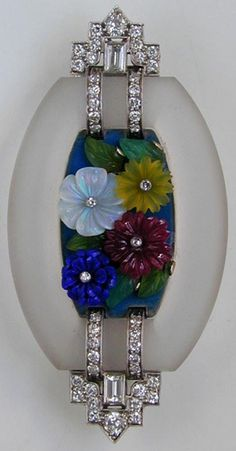An Art Deco rock crystal, diamond and multi gem-set brooch, circa 1920. Centred with four carved flower heads composed of opal, lapis lazuli, red and yellow hardstones, centred with a single cut diamond, with chrysoprase leaves, on a blue ground, with foliate engraved back panel, within a tonneau shaped rock crystal frame and applied diamond highlights to the shoulders, set with a baguette and round brilliant-cut diamonds, white millegrain set, 60 x 30mm.