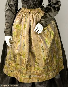 Silk jacquard apron, mid-19th century;   Striped gold and grey silk woven with alternating stripes of moire faille and yellow and green jacquard flowers, handstitched, gathered and smocked waistband, silk cord and tassel, two patch pockets, probably French