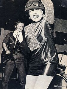 """Poly Styrene (born Marianne Joan Elliott-Said; Lead vocalist for the punk rock band X-Ray Spex, also releasing punk rock solo work. With the band, their first single, """"Oh Bondage Up Yours!"""", is now acknowledged as a classic punk rock single and the album, """"Germfree Adolescents"""", is widely acclaimed as a classic album of the punk rock genre. Her lyrics inspired the riot-grrrl movement, and the anti-consumerist nature of punk music.)"""