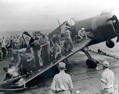 Ship crew put their weight on damaged Wildcat to keep it from falling into sea; 1944