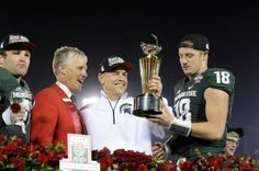 MSU's Kyler Elsworth, head coach Mark Dantonio and quarterback Connor Cook hold up the Rose Bowl Championshi trophy after MSU's 24-20 victory