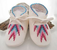 Beaded Baby Moccasins in a soft white deerskin that allows for stretch and comfort. The bead work is a southwest pattern in pinks and teals.