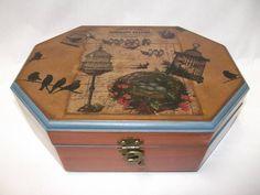Caixa em MDF, oitavada, decorada com pintura envelhecida, transferência. Na parte interna possui várias divisões, bandeja e aneleira, é forrada em tecido. Possui fecho em metal envelhecido. R$ 85,00